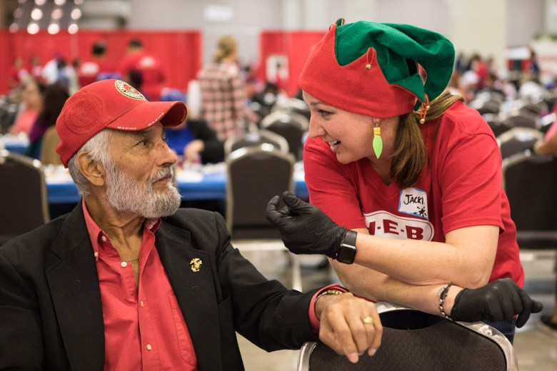 (From left) Phil Reyes chats with H-E-B partner Jackie Moczygemba at the 25th annual H?E?B Feast of Sharing holiday dinner.