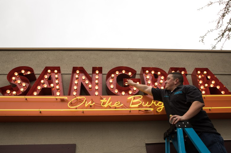 Ceasar Zepeda replaces two lightbulbs in the sign on his restaurant Sangria on the Burg.