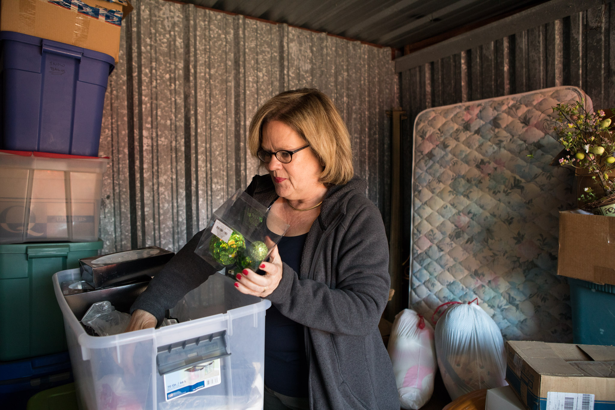 Holly Perry sorts through her Christmas decorations at Ford's Landing Mini Storage.