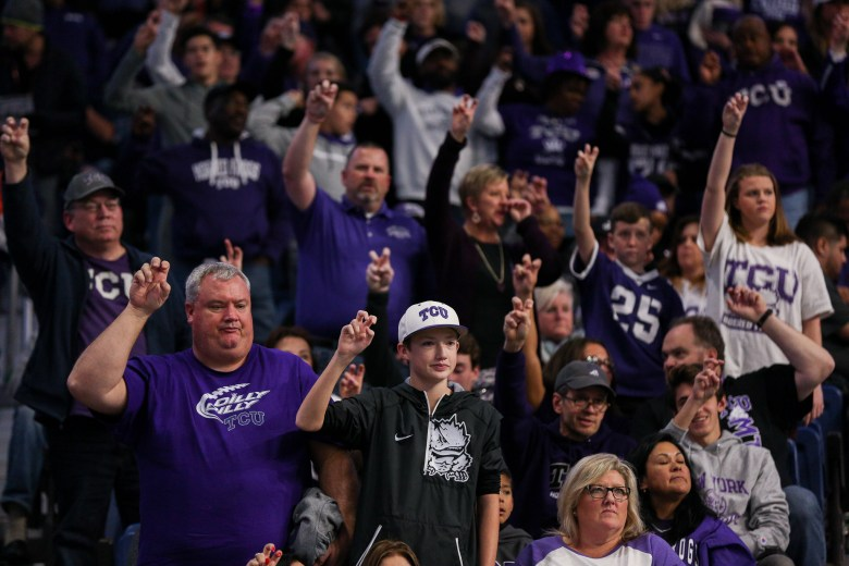 TCU fans raise their hands in school spirit during the TCU fight song.