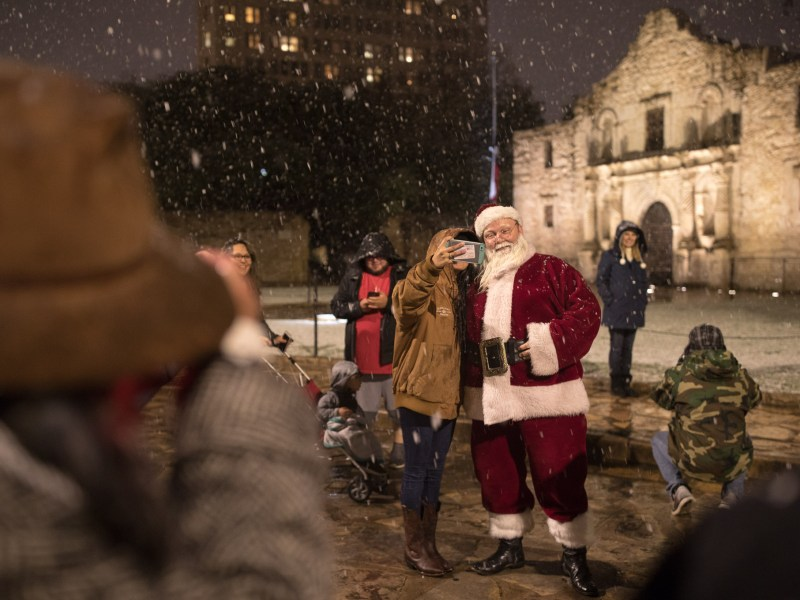 Santa Claus poses for a photo with Alamo visitors.