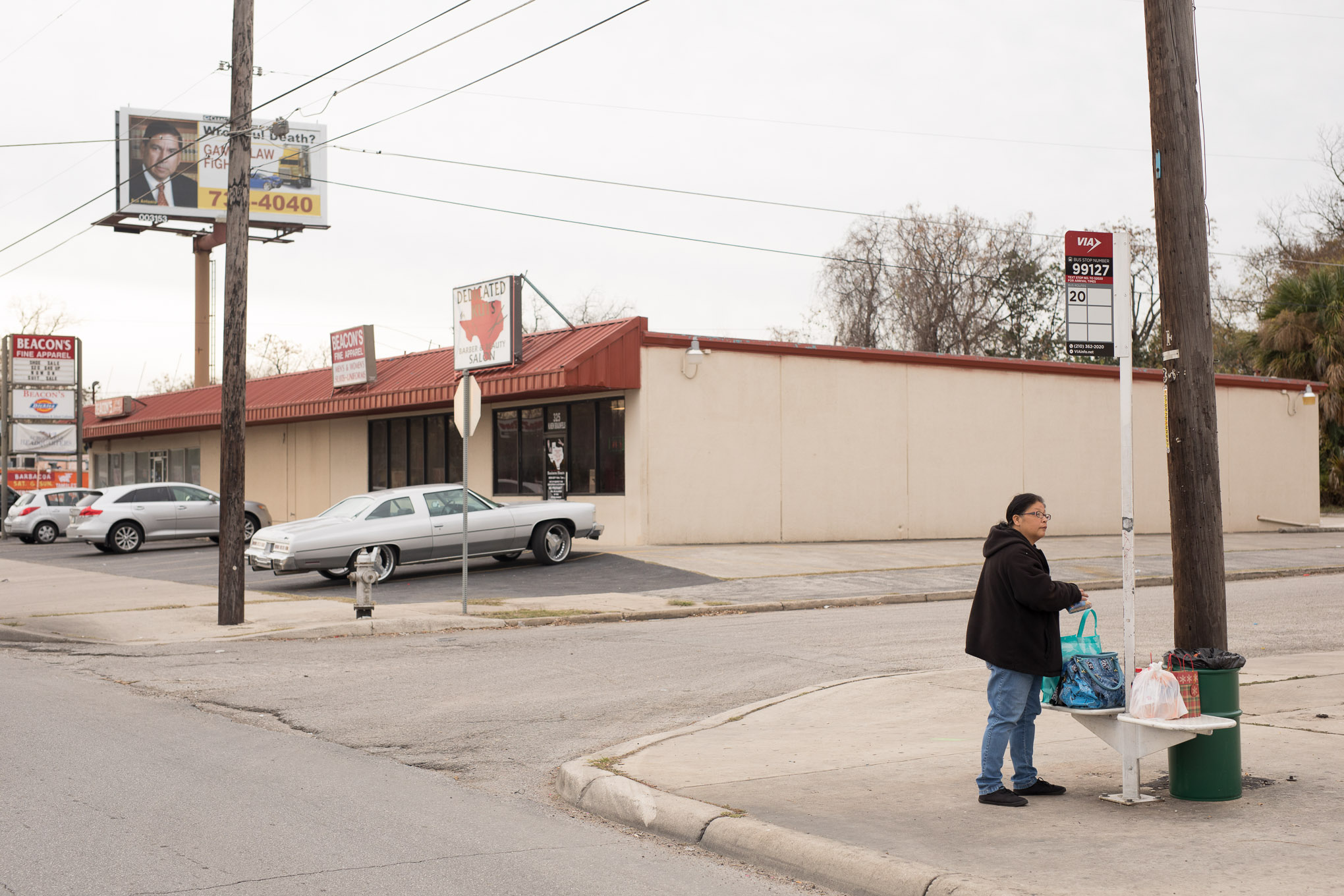 Josie Rios waits at an unsheltered bus stop at the intersection of N. New Braunfels and E. Crockett.