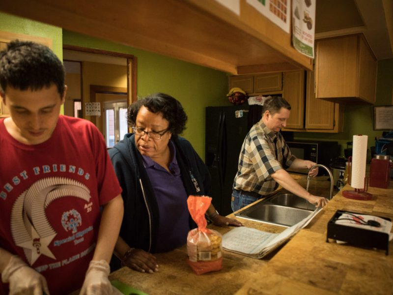 (From left) Douglas Acuff, Autism Treatment Center Residential Coordinator Cynthia Fox, and Michael DeKunder prepare dinner for the house residents.