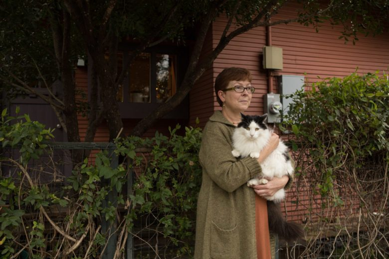 Rose Kanusky holds her cat Kindle at the side entrance of her home in King William.