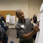Charles Fentry writes down the priorities of his group at SA Climate Ready Town Hall.