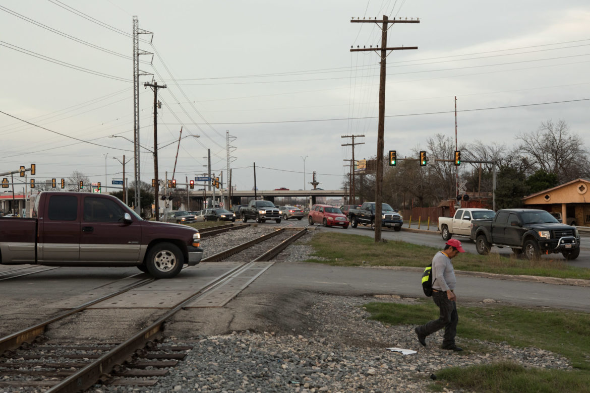 Both car and pedestrian traffic crosses the railroad tracks at the intersection of Zarzamora Street and Frio City Road.