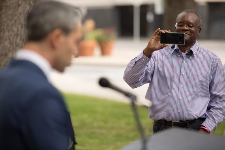 Fire Fighters Association President Chris Steele (right) records the press conference held by Mayor Ron Nirenberg (left).