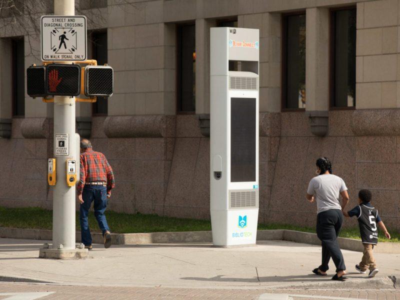 Pedestrians walk near a Bexar Connect smart kiosk alongside the Paul Elizondo Tower.