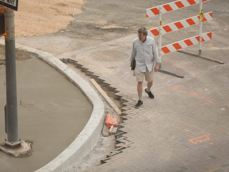 A pedestrian walks along a construction zone at East Houston Street as concrete is poured for a nearby sidewalk.