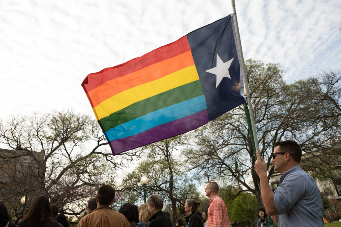 Andrew Perretta holds a pride flag imitating the Texas flag at a rally at Crockett Park to protest a ruling made in the case of Kenne McFadden.