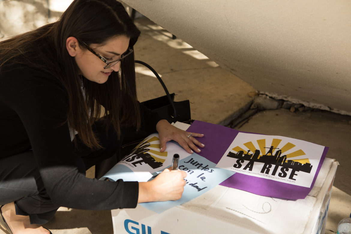 Viridiana Carrizales prepares signs for the announcement of the collaboration between SA RISE, SAISD Police Chief Curiel, and the SAISD district in regards to the handbook about Senate Bill 4.
