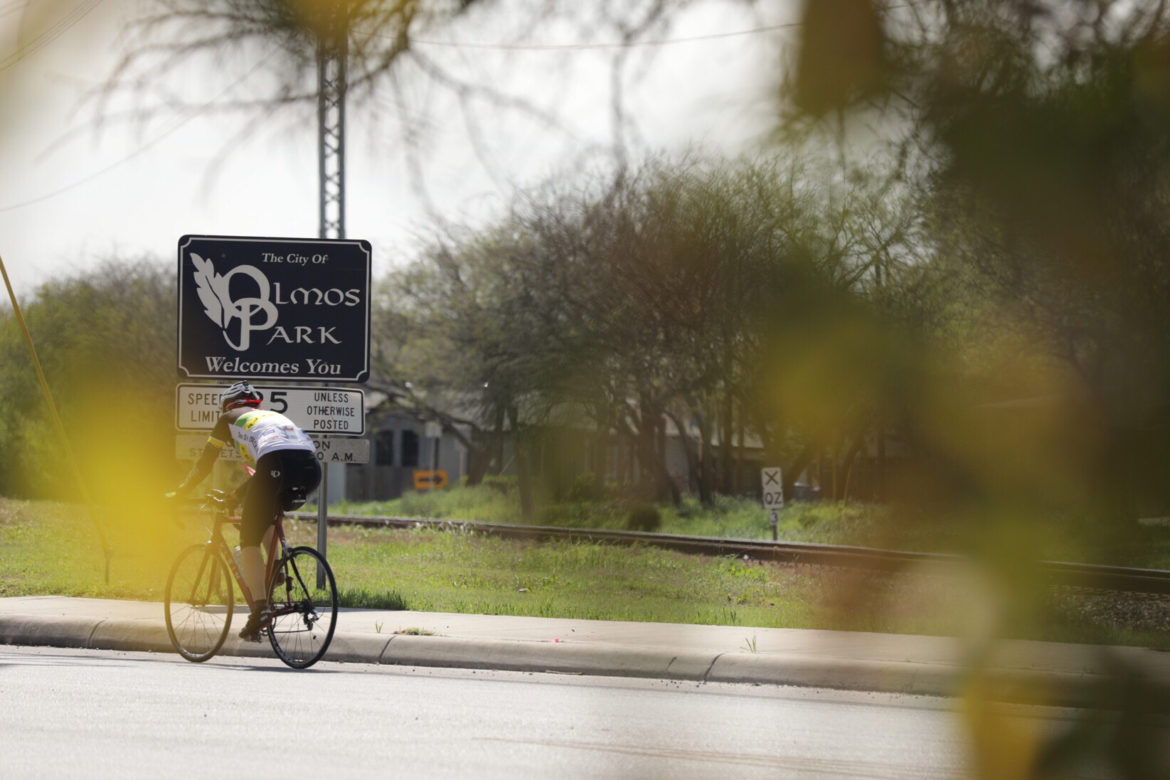 A cyclist rides into the City of Olmos Park on McCullough Avenue.