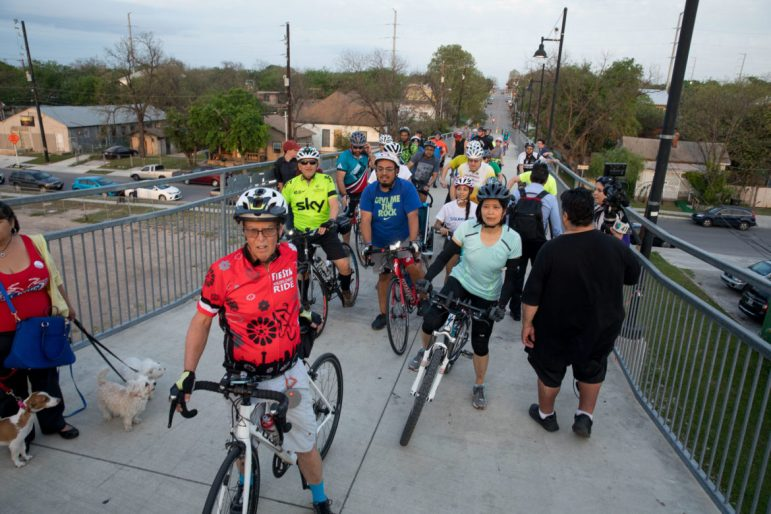 Cyclists pass through the meeting while in progress.