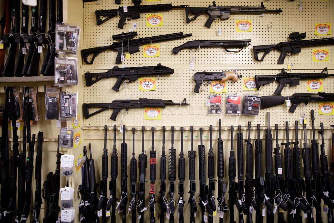 Assault styled weapons are leaned and mounted on the pegboard wall at Nagel's Gun Shop.