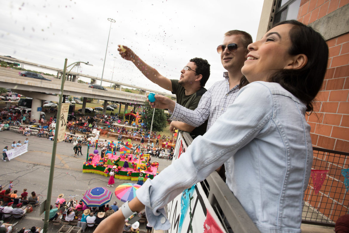 (From left) Mark Teplitsky, Danny Taubenheim, and Brenda Gonzalez throw confetti into the air in celebration of the Battle of Flowers Parade.