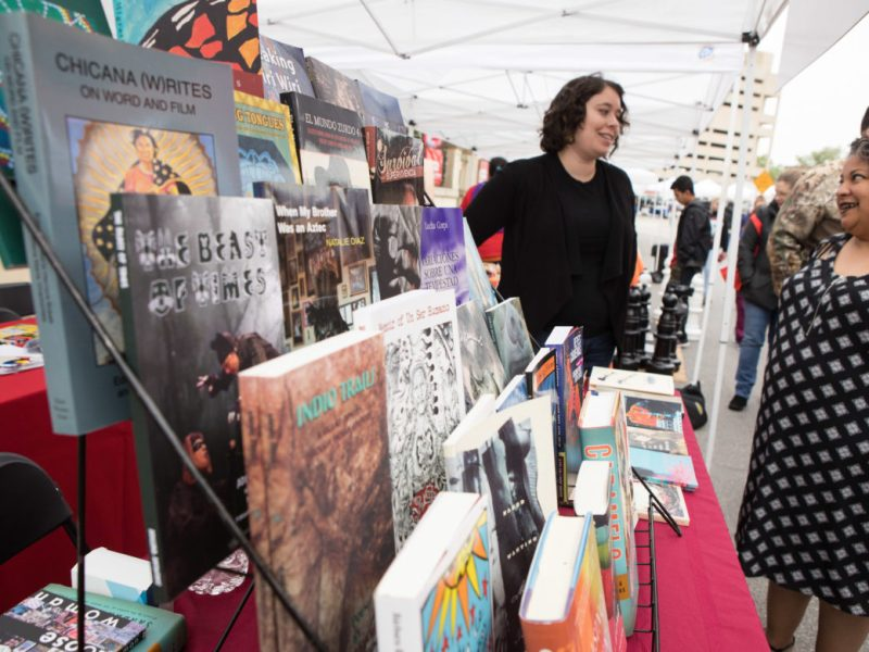 Leticia Urieta, program director of the Austin chapter of Barrio Writers, (left) explains which books are for sale during the 6th annual San Antonio Book Festival.