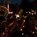 Band instruments are lit up with string lights as they walk down Commerce Street.