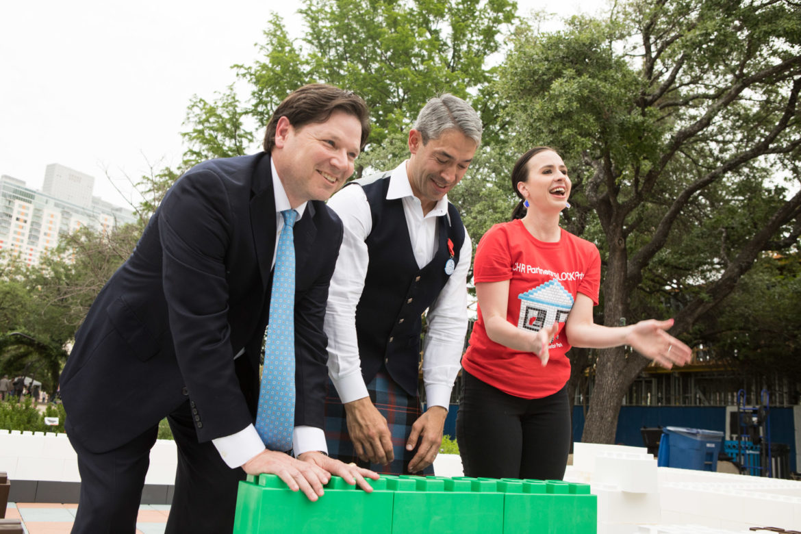 (From left) Vince Fertitta, President of Bank of America, Mayor Ron Nirenberg, and Meghan Garza-Oswald, Community Housing Resource Partners executive director, symbolically build a house during the ¡Viva Hemisfair! Friday Kick-Off at Yanaguana Garden.