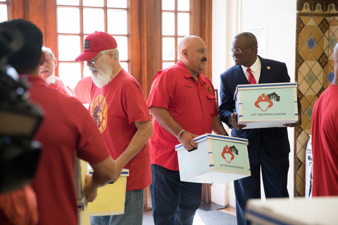 San Antonio Professional Firefighter Union President Chris Steele (right) delivers petitions to City Hall.