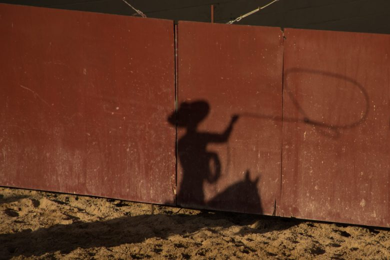 Luis Parra Villanueva's shadow is projected on the arena wall as he rides Bloodbuzz in their first charreada together.