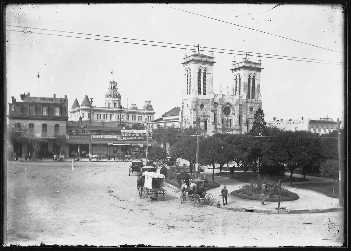 The original 1889 City Hall (left) building rises above other buildings near San Fernando Cathedral (right).