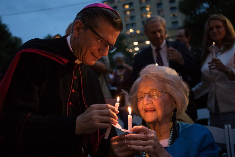 Archbishop Gustavo García-Siller lights Rosemary Kowalski's candle during the candlelight vigil.