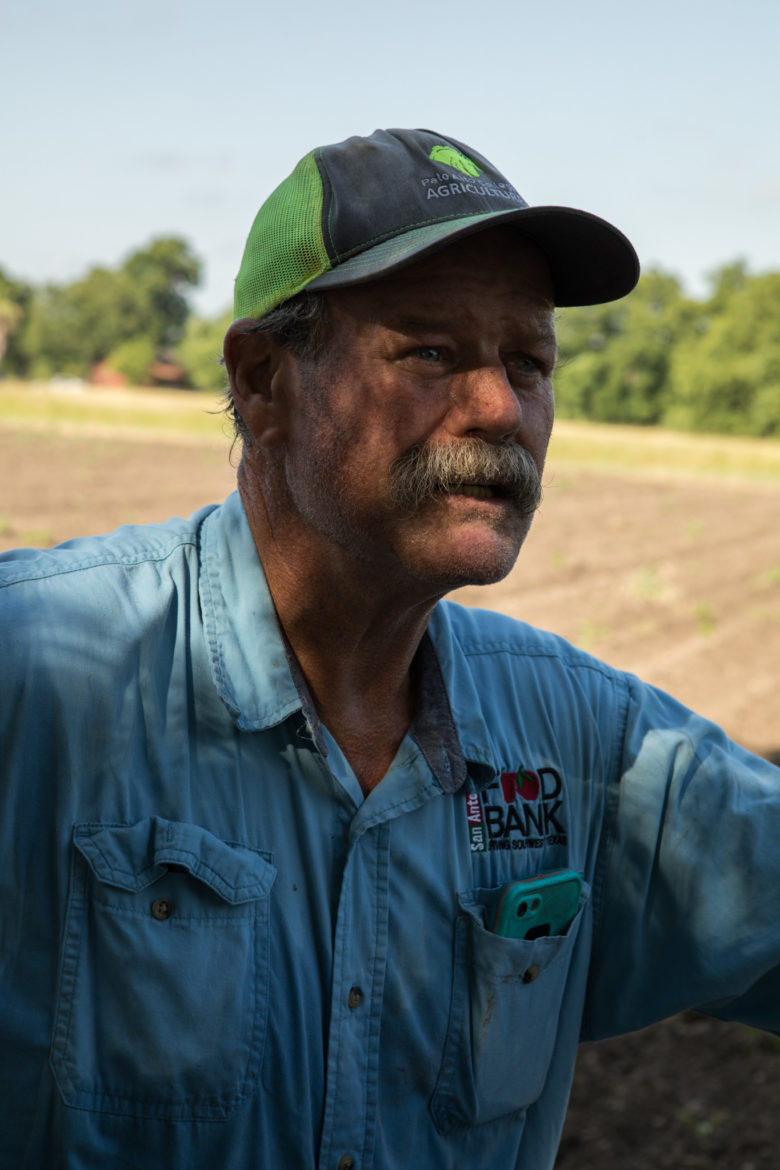 Mike Persyn, a farmer for the San Antonio Food Bank, diverts water from the San Juan Acequia to a demonstration garden near the mission.