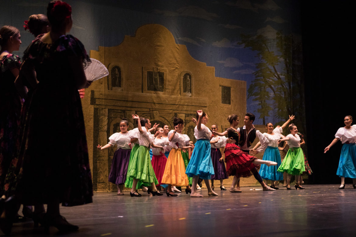 A large group of dancers practices their choreography on stage during the dress rehearsal.