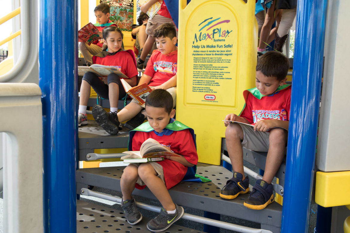 Students read books at the launch of the Super Summer Readers Program on Mays Boys & Girls Club playground.