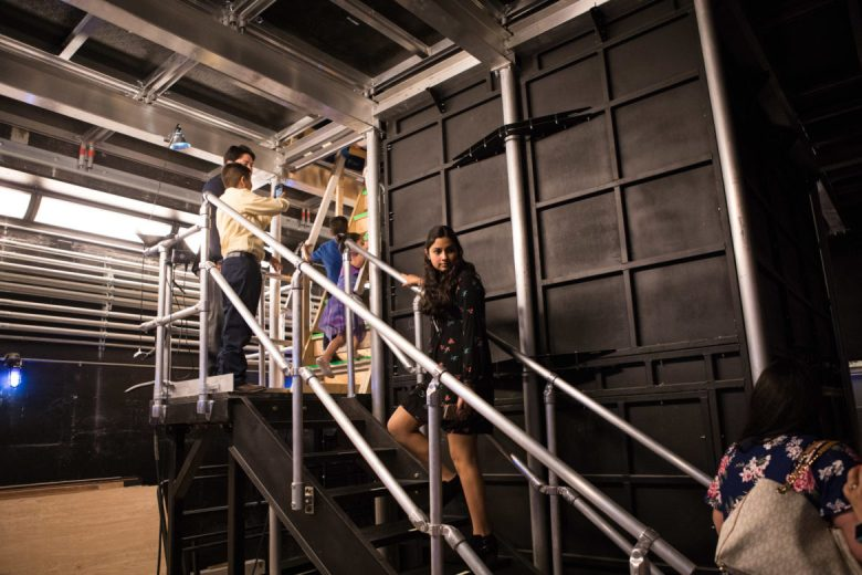 Alexia Farias, Anne Frank Inspire Academy 7th grader and first place winner, climbs up the stairs to the trap door of the set.