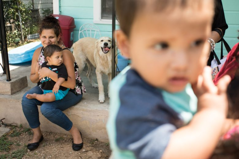 (From left) Monica Lara and her sons Jordan and Julian play in their neighbor and promotora's front yard.
