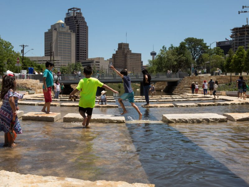 Children run through the water at San Pedro Creek Culture Park on opening day of the first segment.