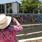 "A woman takes a photo of the mural ""De Todos Caminos Todos Somos Uno"" by Adriana M. Garcia along San Pedro Creek."