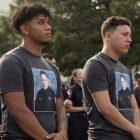 (From left) Matthew Carson and Ray Garcia wear t-shirts honoring Scott Deem.