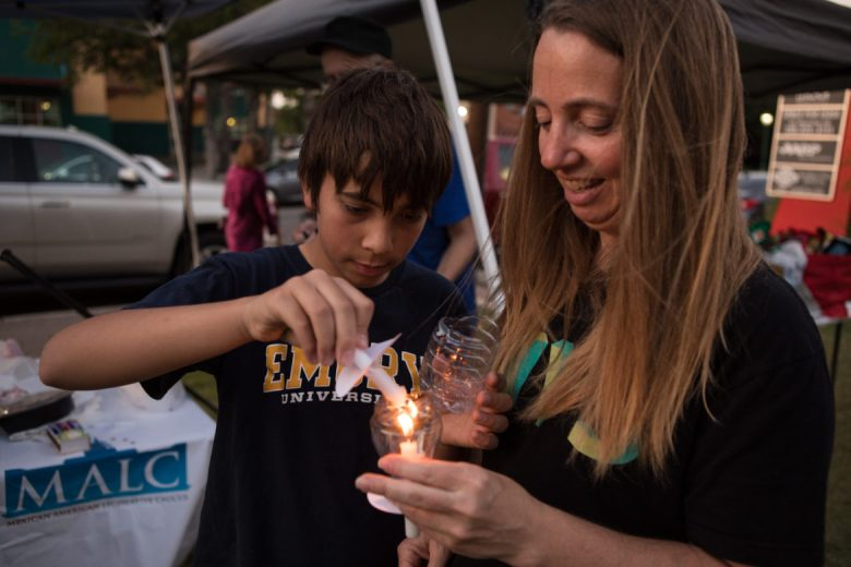 (From left) Gabriel, 11, and Danielle Miller protect their candles from the wind with water bottles.
