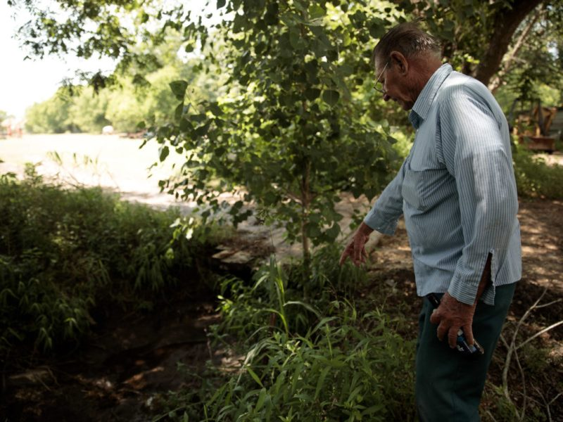 Arthur Maspero points to the acequia that runs through his land, the same waterway that his father used before him to irrigate crops to be sold downtown.