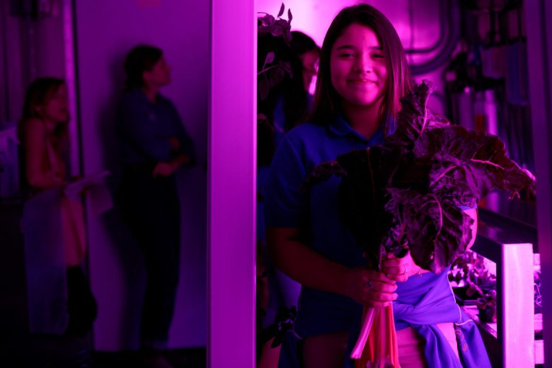 Laila Rodriguez, an eighth-grade student at IDEA Public Schools' Eastside campus, holds a bushel of chard that was produced inside a shipping container.