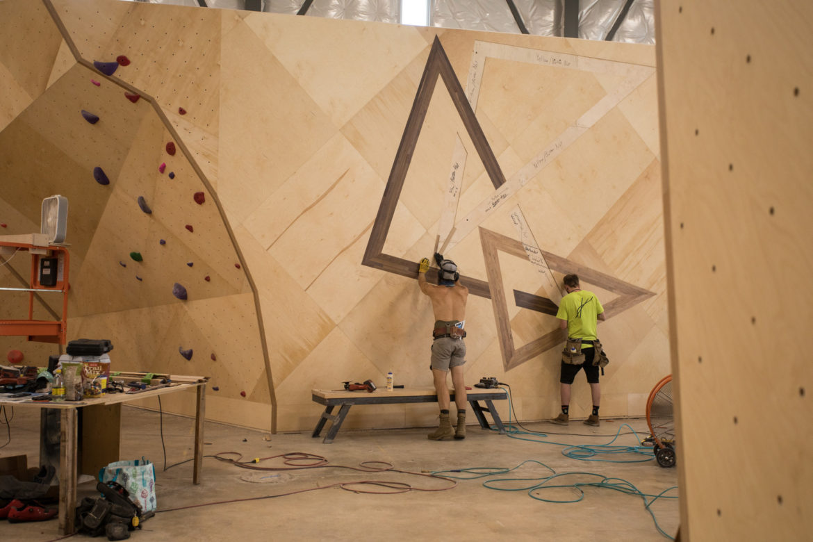 Construction workers create the logo wall.
