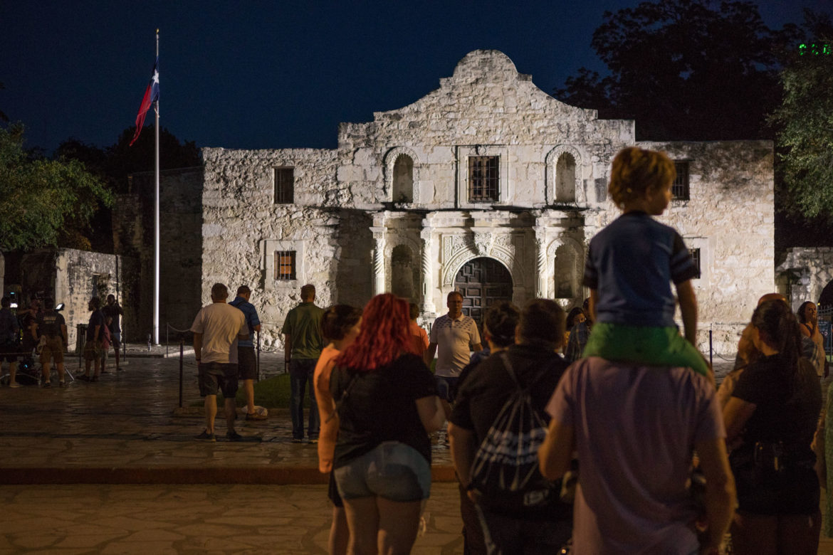 A boy sits on an adult's shoulders in front of the Alamo.