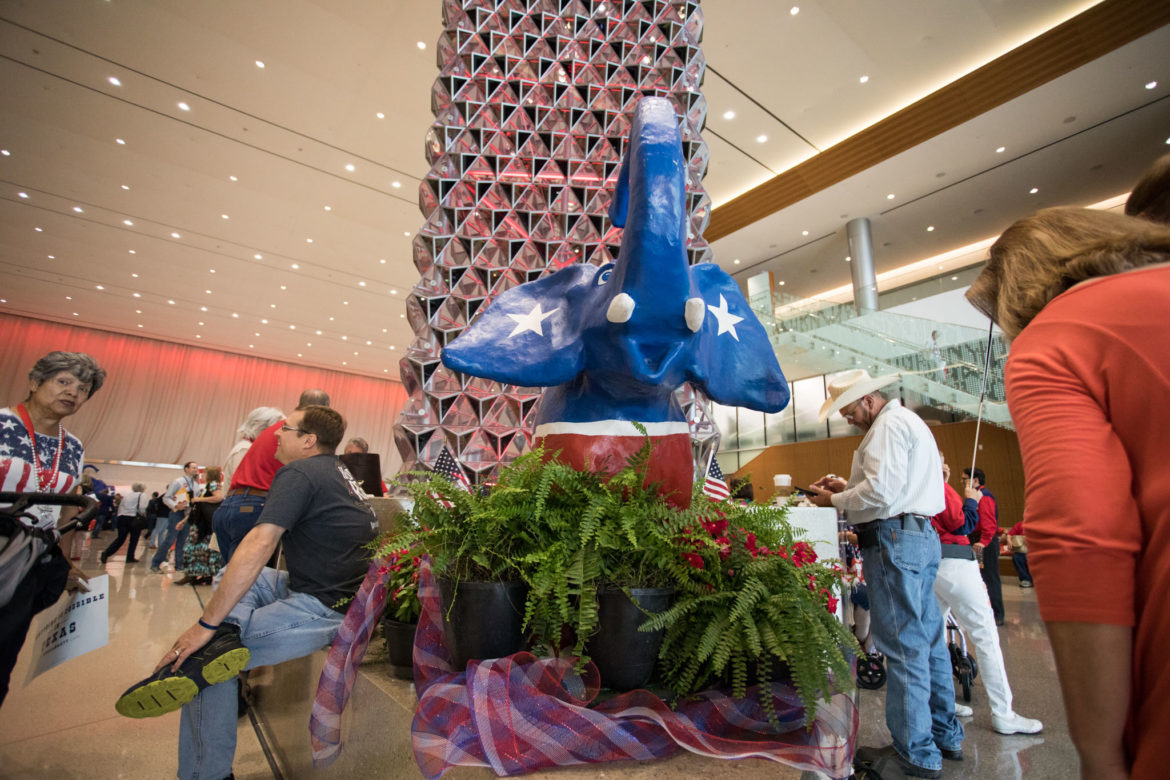 Attendees stand next to the Republican elephant statue.