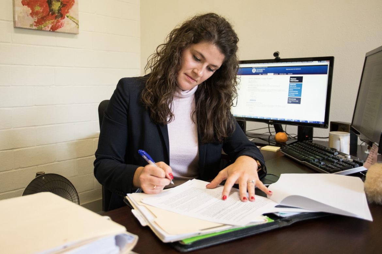 Katie Mullins, RAICES staff attorney, works on paperwork in her office.