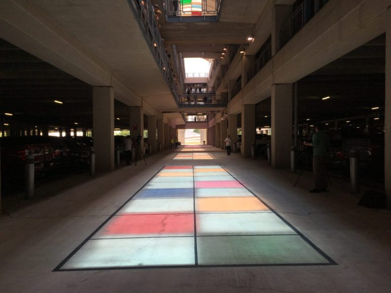 As the sun approaches its apex on the longest day of the year, it illuminates Passing Light, a public art installation by Christopher Janney in the breezeway of the San Antonio International Airport long-term parking structure.