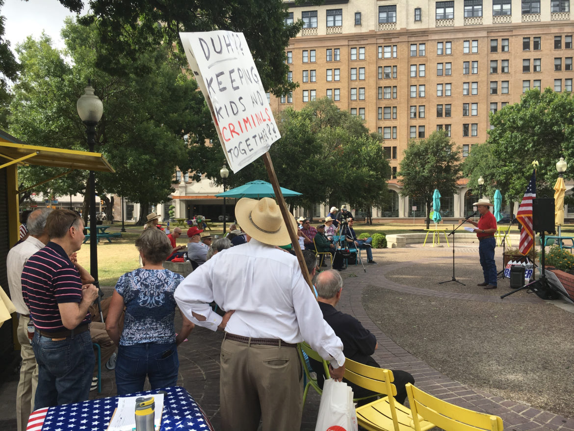 """About fifty people gathered in Travis Park for the """"America First"""" event."""