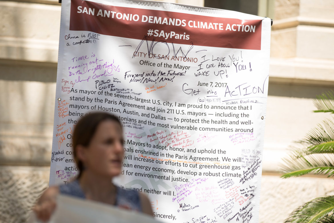 A printed poster that reads the announcement from San Antonio Mayor Ron Nirenberg that the city of San Antonio will stand by the Paris Agreement.