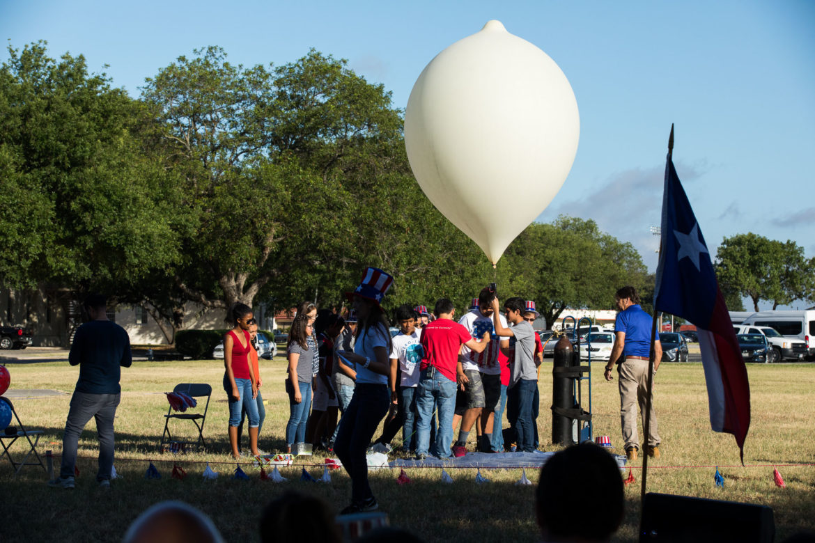 Students gather around holding the rope attached to the high altitude balloon at Port San Antonio.