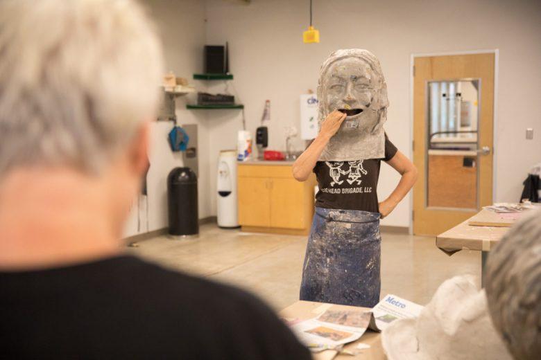 Neus Hosta tries on a work in progress sculpture at the Southwest School of Art.