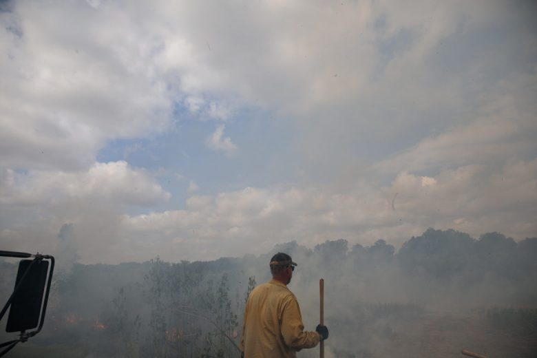 Wildlands Firefighter Jeff Gosling looks over the large swath of land that is currently in flames.