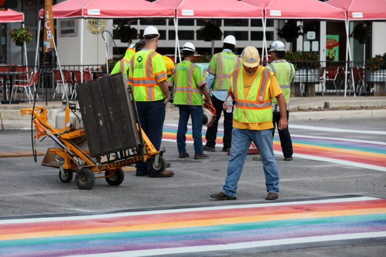 Construction workers inspect the nearly finished rainbow crosswalk at North Main Avenue and West Evergreen Street.