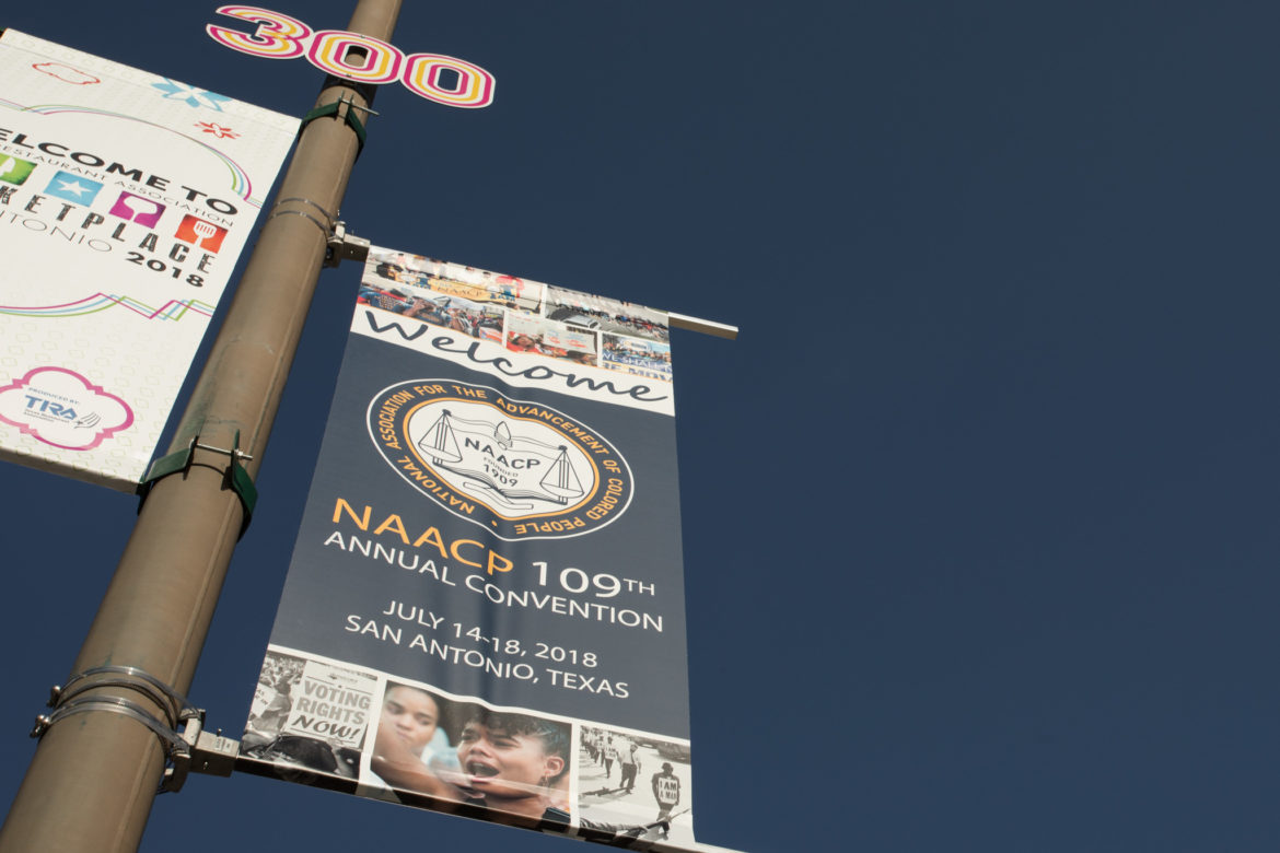 Signage announcing the NAACP 109th Annual Convention hangs outside of the Henry B. Gonzalez Convention Center.