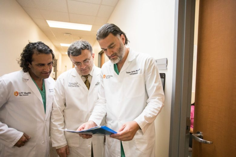 (From left) Cardiologist S. Hinan Ahmed, Vascular / Endovascular surgeon Mark Davies, and Orthopedic surgeon Thomas Zgonis share notes on a patient.